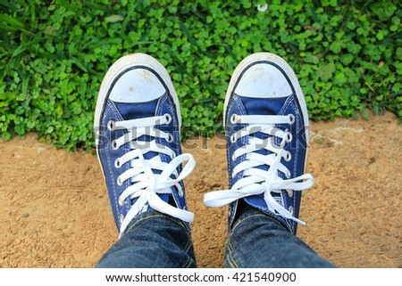 Legs wearing blue jeans and blue sneakers - stock photo