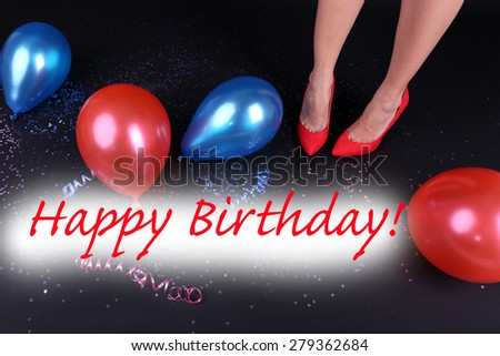 Legs with confetti and balloons on the floor - stock photo