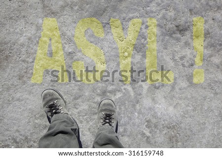 legs with gray boots and the word Asyl in german language on the ground. Concept for Refugees on their way to Germany. - stock photo