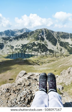 Legs with hiking boots  of hiker woman traveler  sitting in the summer mountain . Freedom concept