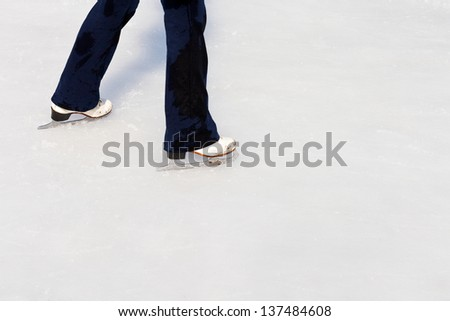 legs with skates on ice of outdoor open skating rink