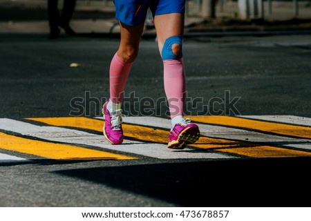 legs women athletes in compression socks and taping knee running sports race