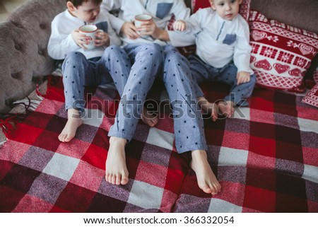 legs young brothers in identical pajamas holding mugs of milk sitting on a sofa in the dining room - stock photo