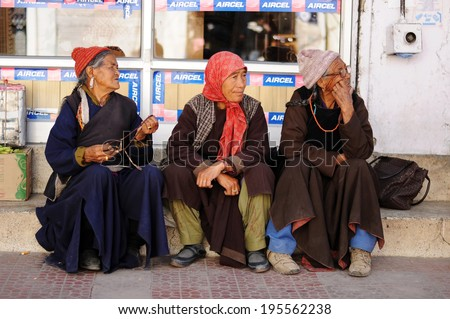 LEH IN LADAKH, INDIA - SEPTEMBER 17 2012: Old unidentified local women sitting on the street of Leh. The majority of the local population are descendant of Tibetan. - stock photo