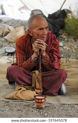 LEH IN LADAKH, INDIA - SEPTEMBER 17 2012: Unidentified old buddhist monk is praying outside the monastery in Leh. The majority of the local population are descendant of Tibetan. - stock photo