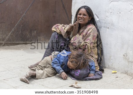 LEH, INDIA - JUNE 24, 2015: Unknown beggar woman with a child begging near a Buddhist temple in Leh, Ladakh. Poverty is a major issue in India - stock photo