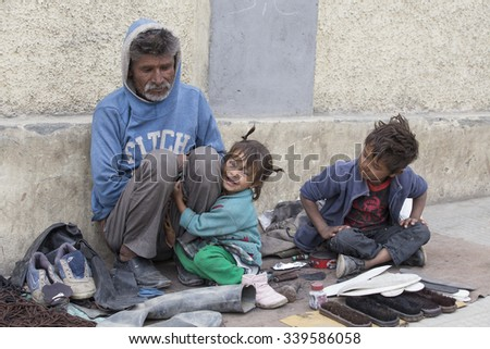 LEH, INDIA - SEPTEMBER 08, 2014: An unidentified beggar family begs for money from a passerby in Leh. Poverty is a major issue in India - stock photo