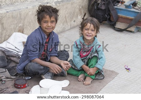 LEH, INDIA - SEPTEMBER 08, 2014 : An unidentified beggar girl and boy beg for money from a passerby in Leh. Poverty is a major issue in India - stock photo
