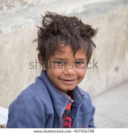 LEH, INDIA - SEPTEMBER 08 2014: Unidentified beggar boy begs for money from a passerby in Leh. Poverty is a major issue in India - stock photo