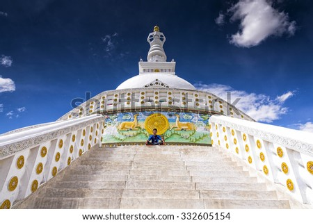 Leh, Ladakh - August 24, 2015: View of a young boy meditating in front of Shanti Stupa. Shanti is a Buddhist white-domed stupa on a hilltop in Chanspa, Leh district. It was built in 1991. - stock photo