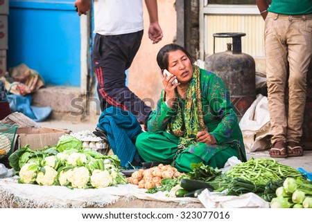 LEH LADAKH , INDIA - AUGUST 11 : The local woman are talking mobile phone and selling vegetables on the street market in Leh Ladakh,India on August 11, 2015.