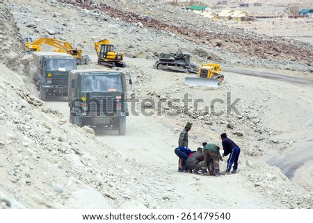 Leh, Ladakh, India - MAY 05: Stone slide blocking the road on amazing roads along the high mountain to Chang-La Pass, more than 5,400 metres above sea-level in Ladakh, India. May 05, 2014 - stock photo