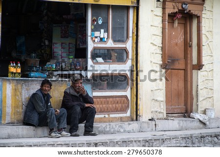 LEH LADAKH, INDIA-MAY 2014:Two tibetan sit in front of minimart.