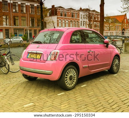 LEIDA, NETHERLANDS - APRIL 26, 2015: Fiat 500 in pink color along city canal. Fiat is a subdivision group of great autumobiles group FCA. - stock photo