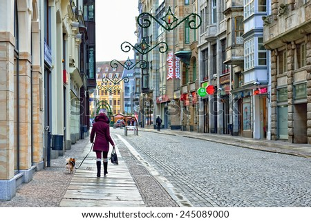LEIPZIG, GERMANY-DECEMBER 21, 2014: Person walking by decorated for Christmas shopping street in historical center of Leipzig - stock photo
