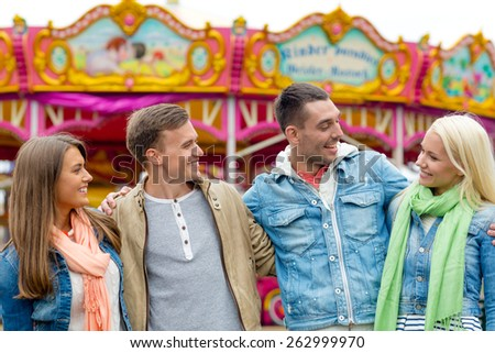 leisure, amusement park and friendship concept - group of smiling friends with carousel on the back - stock photo