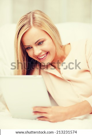 leisure and education concept - smiling woman lying on the couch with tablet pc