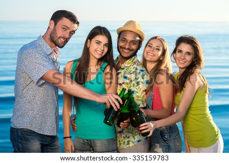 Leisure at sea. Weekend abroad. Youth party at sea. Funny guys and girls resting on vacation. Young people drink beverages on the beach.