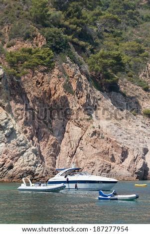 Leisure boats lazily anchored off an coast. Close up - stock photo