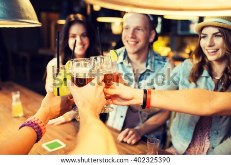 leisure, celebraton, friendship, people and holidays concept - happy friends clinking glasses at bar or pub - stock photo