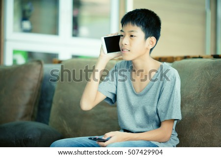 leisure, children, technology, communication and people concept - smiling boy calling on smartphone and watching TV at home