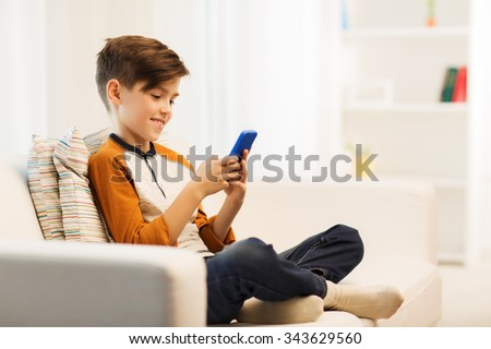 leisure, children, technology, internet communication and people concept - smiling boy with smartphone texting message or playing game at home - stock photo