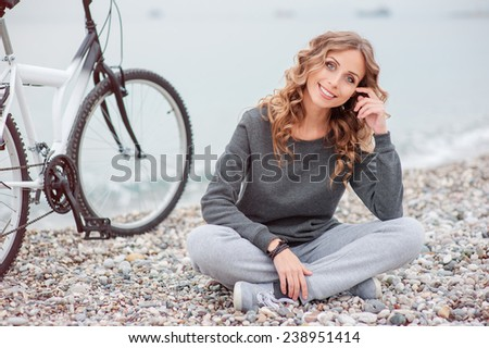 Leisure day at the beach. Attractive young blond woman with beautiful curl long hair sitting with a bicycle near the sea. - stock photo