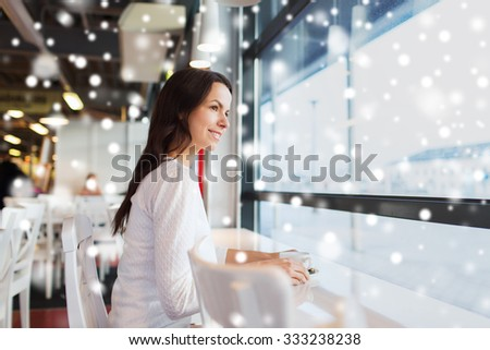 leisure, drinks, people and lifestyle concept - smiling young woman drinking coffee at cafe with snow effect - stock photo