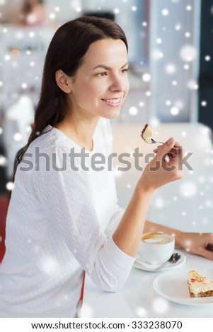 leisure, drinks, people and lifestyle concept - smiling young woman eating cake and drinking coffee at cafe with snow effect - stock photo