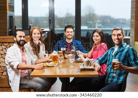 leisure, eating, food and drinks, people and holidays concept - smiling friends having dinner and drinking beer at restaurant or pub - stock photo