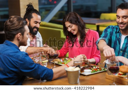 leisure, eating, food, people and holidays concept - smiling friends having dinner and tasting each other dish at restaurant - stock photo