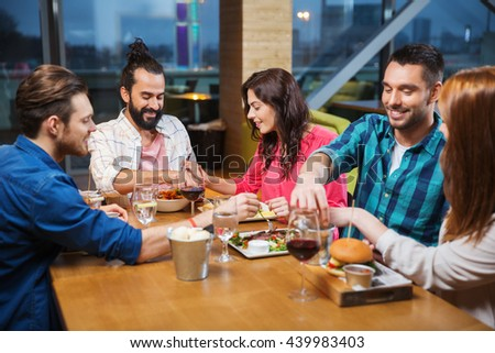 leisure, eating, food, people and holidays concept - smiling friends having dinner and tasting each other dish at restaurant