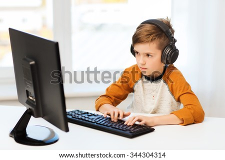 leisure, education, children, technology and people concept - boy with computer and headphones typing on keyboard or playing video game at home