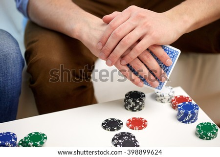 leisure, games, friendship, gambling and entertainment - close up of male hand with playing cards and chips at home - stock photo