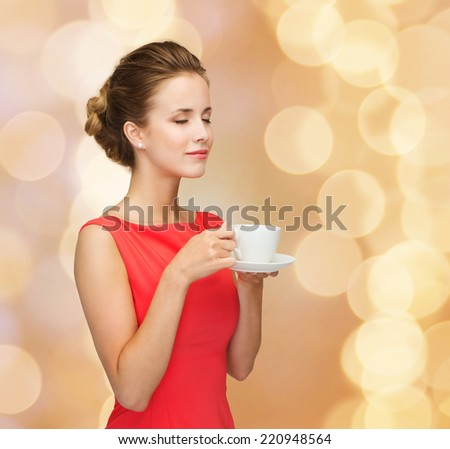 leisure, happiness and drink concept - smiling woman in red dress with closed eyes holding cup of coffee over golden lights background - stock photo