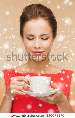 leisure, happiness and drink concept - smiling woman in red dress with cup of coffee over beige background and snow - stock photo