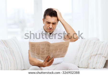 leisure, information, people and mass media concept - sad man reading newspaper at home