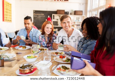 leisure, payment and people concept - happy friends with money paying for food at restaurant