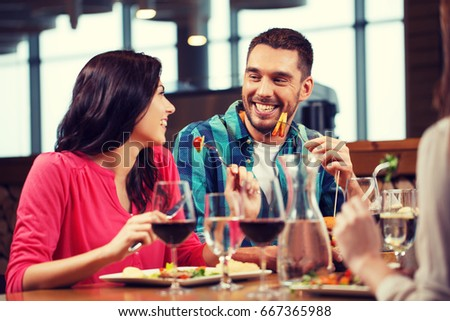 leisure, people, eating and holidays concept - happy couple with friends having dinner at restaurant