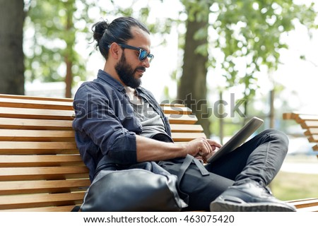 leisure, technology, communication, travel and people concept - man with tablet pc computer and bag sitting on city street bench