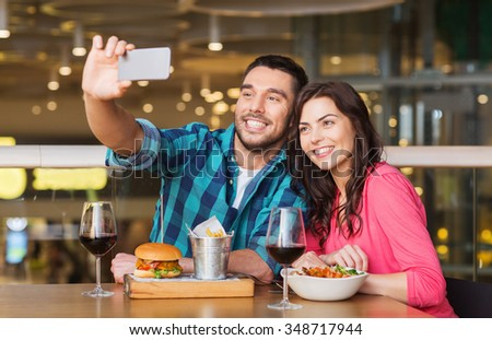 leisure, technology, date, people and holidays concept - happy couple having dinner and taking selfie by smartphone at restaurant - stock photo