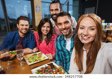 leisure, technology, friendship, people and holidays concept - happy friends having dinner and taking selfie by smartphone at restaurant - stock photo