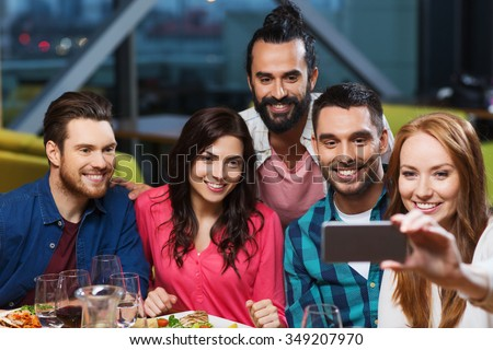 leisure,technology, friendship, people and holidays concept - happy friends having dinner and taking selfie by smartphone at restaurant - stock photo