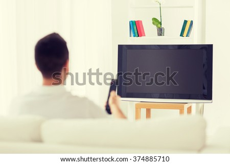 leisure, technology, mass media and people concept - man watching tv and changing channels at home from back - stock photo