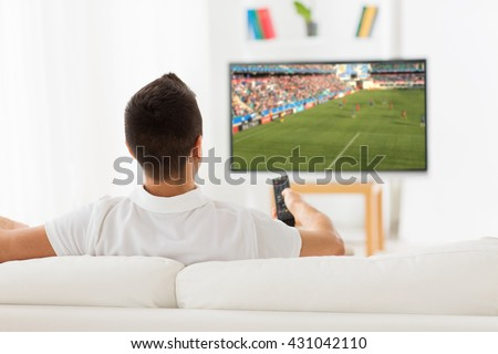 leisure, technology, sport, entertainment and people concept - man with remote control watching football or soccer game on tv at home - stock photo