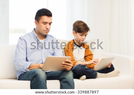 leisure, technology, technology, family and people concept - father and son with tablet pc computer networking or playing at home