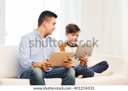 leisure, technology, technology, family and people concept - happy father and son with tablet pc computer networking or playing at home