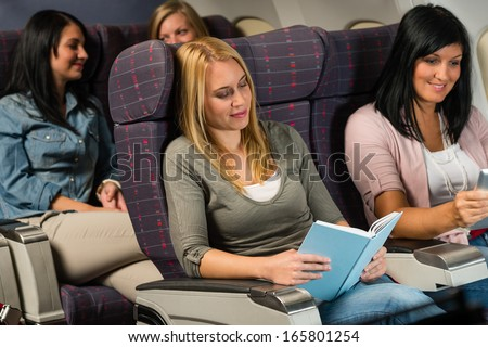 Leisure travel young woman passenger read book airplane cabin flight - stock photo
