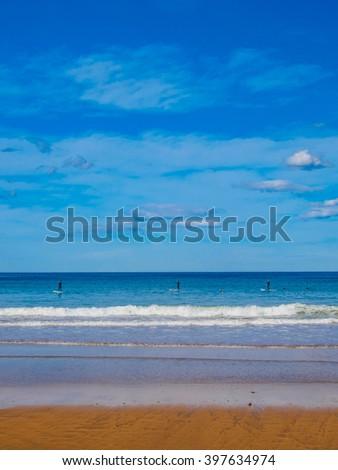 Lekeitio beach island on sunny day paddle surf - stock photo