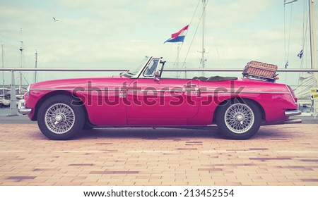 LELYSTAD, THE NETHERLANDS - JUNE 15, 2014: 1967 Red MG B on display during the annual National Oldtimer day. Filtered toned photograph in a retro nostalgic style.  - stock photo